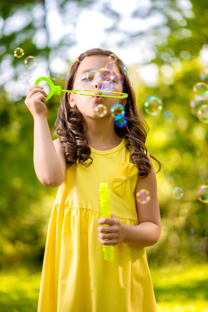 Little girl with soap bubbles